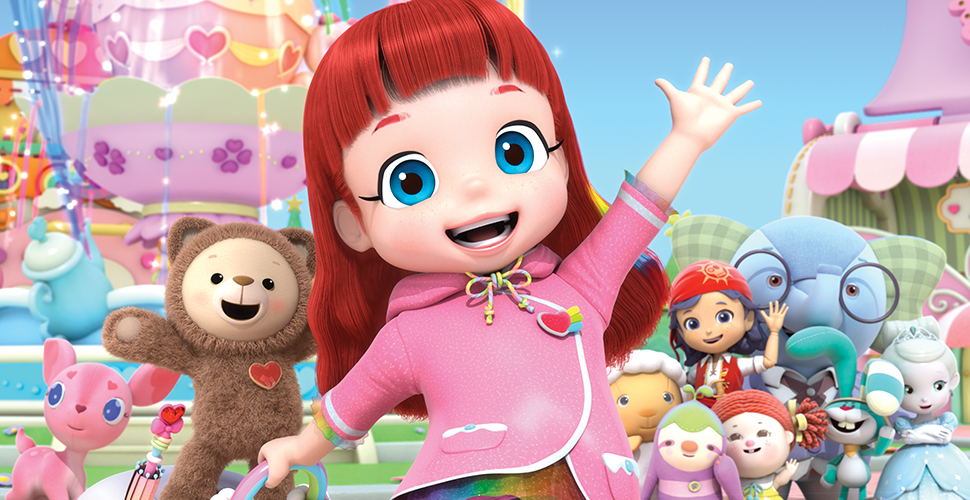 A close-up of a fair-skinned, red haired girl waving and looking excited. In the background, there is a ferris wheel and a group of kids and toys waving.