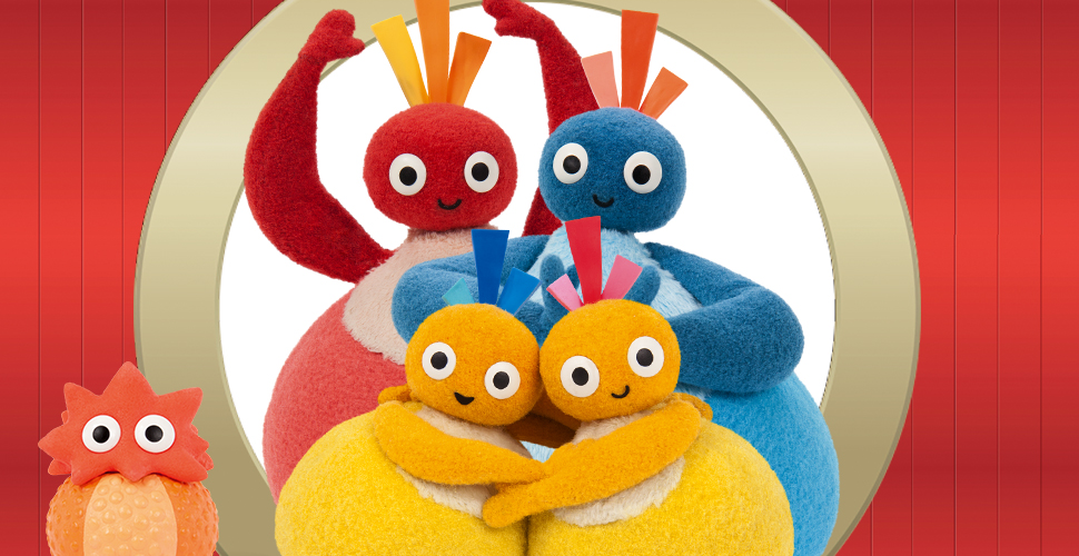 Two round, yellow characters hugging. Behind them are two, bigger blue and red characters. They are standing in front of a white circle on a red background. On the left side is a small, round, orange character.