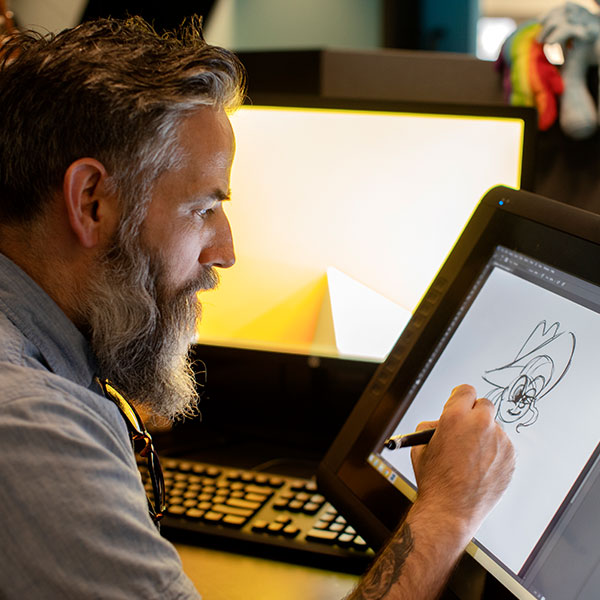 A bearded man sitting at a desk illustrating on a computer monitor.