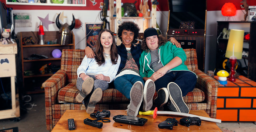 Two teenage boys and a teenage girl sitting on the couch in a basement. They are sitting close to each other with their feet on the table. The table if filled with remotes and video game controllers.