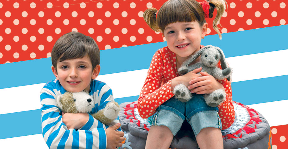 A boy, wearing a white and blue striped shirt, sitting, and hugging a plush toy. Beside him is a girl in a red and white polka dot shirt, sitting on a cushion and holding a plush toy. Behind them are two different backgrounds: one is red with white polka dots and the other is blue with white stripes.