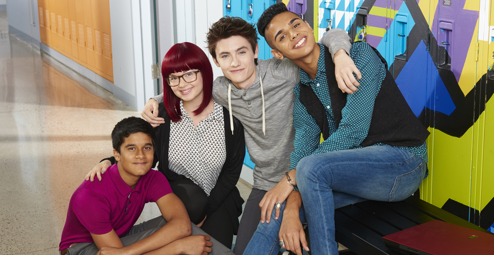 Three teenage boys and one teenage girl hugging and smiling at the camera in a school hallway. Two boys are sitting on a bench and the other two teenagers are crouching.