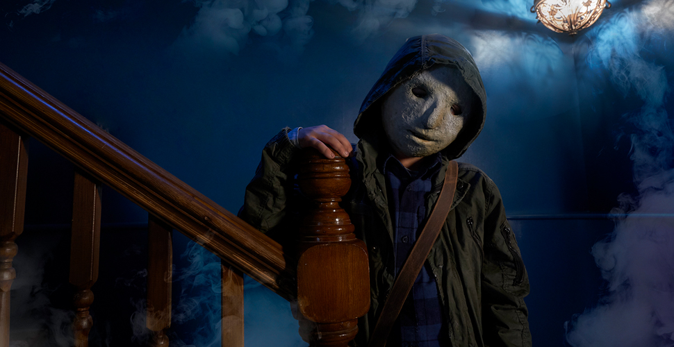 A boy, wearing a creepy white mask, leaning on a railing. He is standing in front of a dark blue, smokey background.